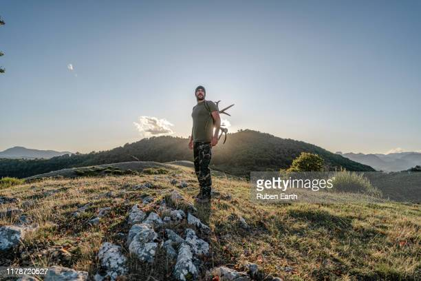 full length portrait of a man in hunting clothing in the mountains with antlers - extreem terrein stockfoto's en -beelden