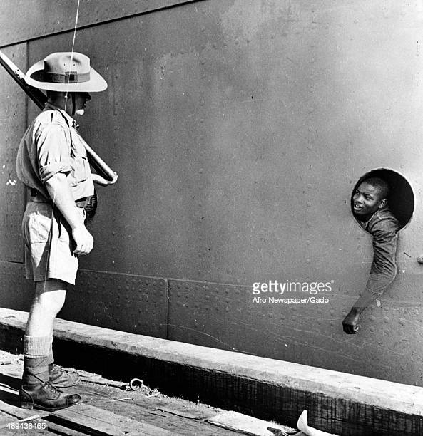A full length portrait of a soldier with shouldered rifle standing on a quay and talking to a soldier looking through a porthole of a ship en route...