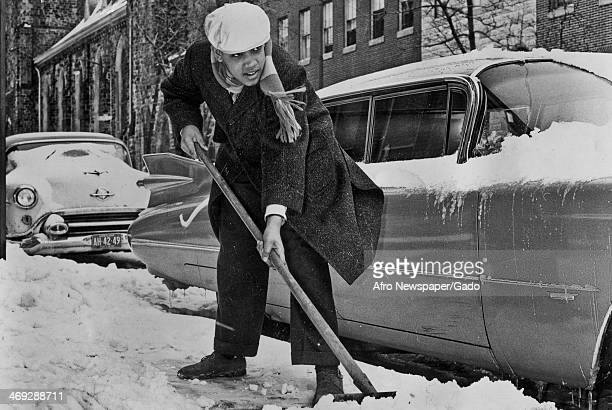 A full length portrait of a teenage boy shovelling snow on a pavement 1960
