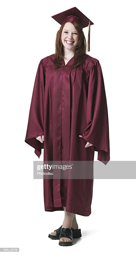 full length portrait of a teenage female graduate in a cap and gown as she smiles : Foto de stock