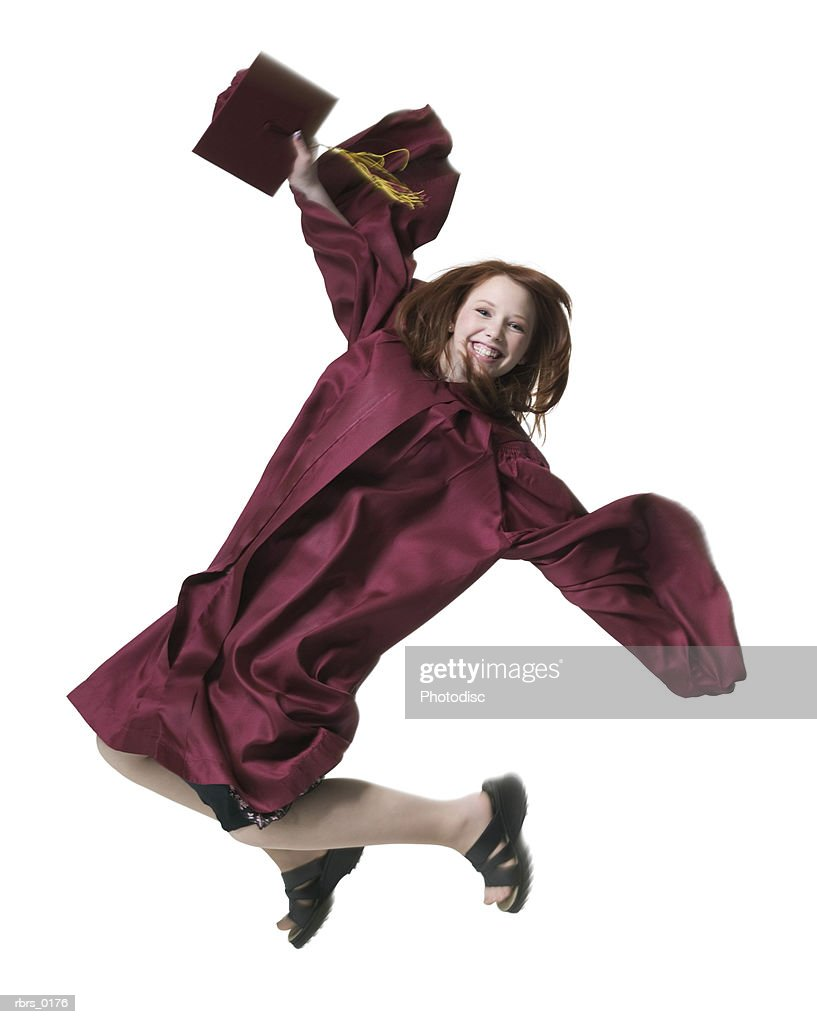 full length portrait of a teenage female in her graduation gown as she jumps through the air : Foto de stock
