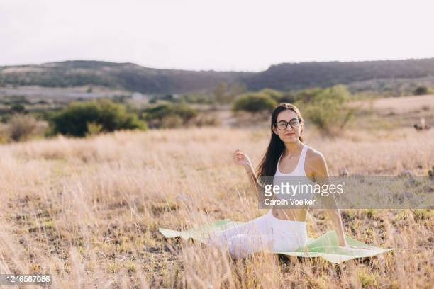 full length portrait of a woman aged 20-29 years sitting on an exercise mat in nature looking at the camera - 2020 2029 stock pictures, royalty-free photos & images