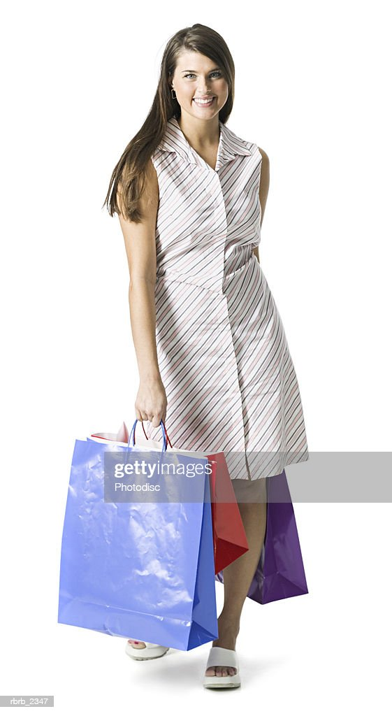 full length portrait of a young adult brunette woman in a stripped dress with shopping bags : Foto de stock