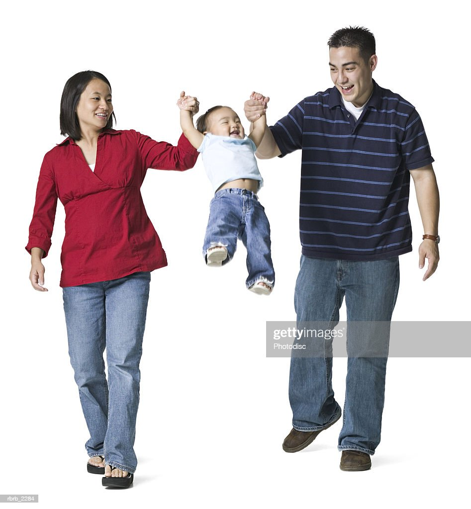 full length portrait of a young adult couple as the hold hands with a swing their young daughter : Stockfoto