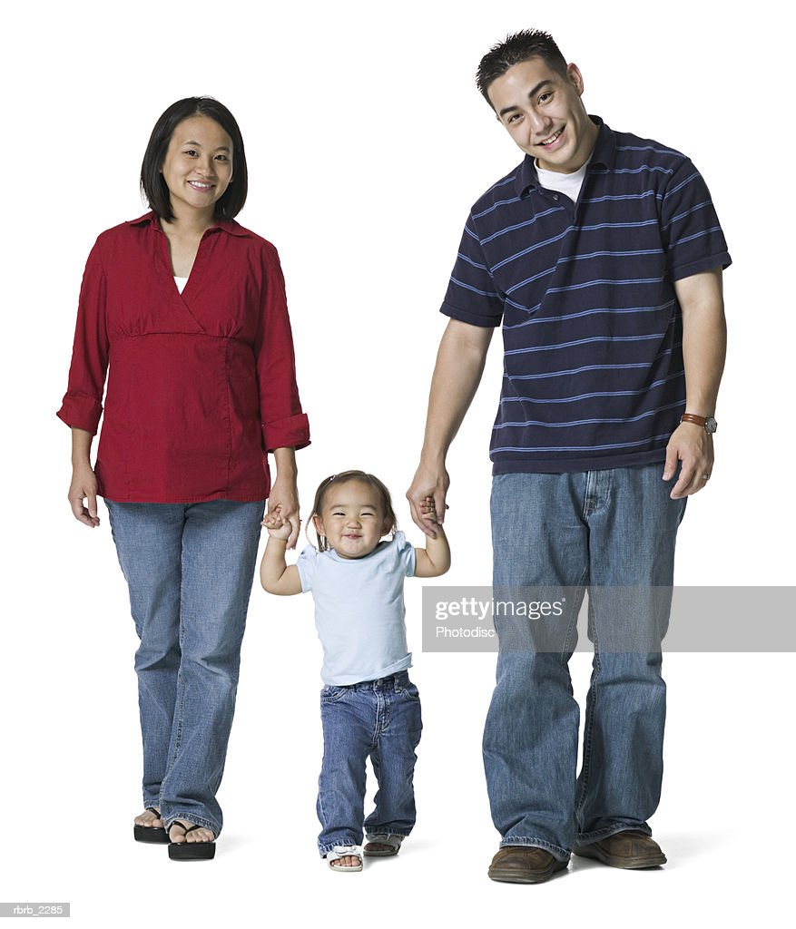 full length portrait of a young adult couple as the hold hands with their young daughter : Foto de stock