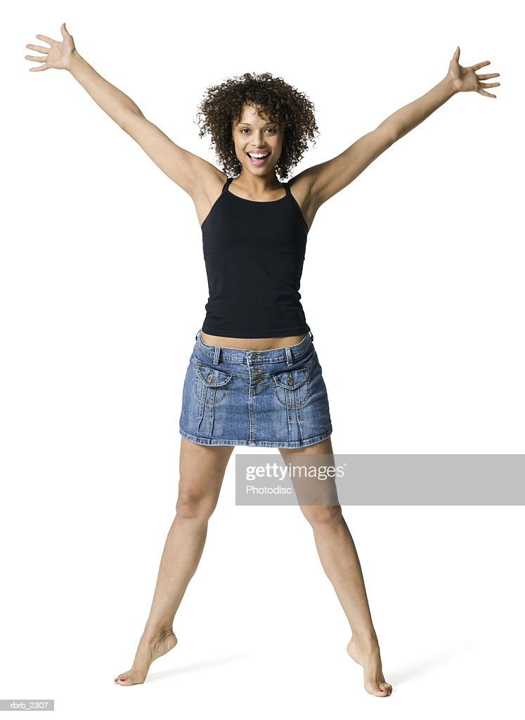 full length portrait of a young adult woman in a black tank top as she throws out her arms : Foto de stock