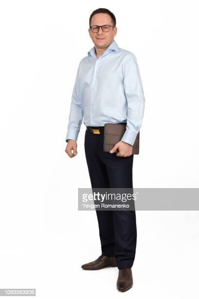 full length portrait of a young man in glasses, formal shirt and trousers with brown folder in hand, isolated on white background - black trousers stock-fotos und bilder