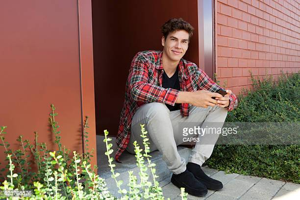 Full Length Portrait Of A Young Man Sitting Outdoor