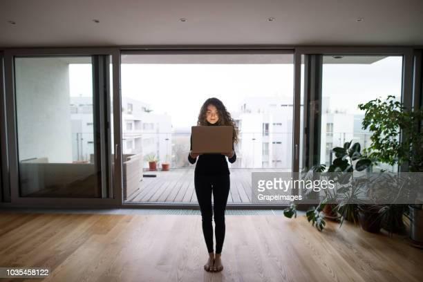 een volledige lengte portret van een jonge tienermeisje permanent blote voeten thuis, laptop voor haar bedrijf. - voor stockfoto's en -beelden