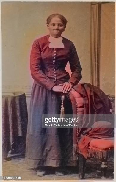 Full length portrait of activist Harriet Tubman looking directly at the camera with folded hands resting on back of an upholstered chair, 1871....