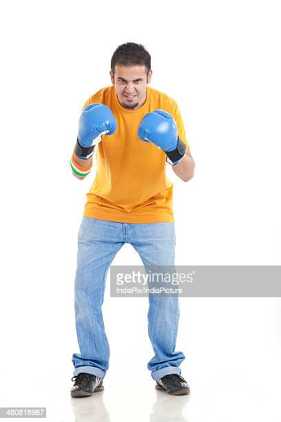 Full length portrait of aggressive male boxer standing over white background