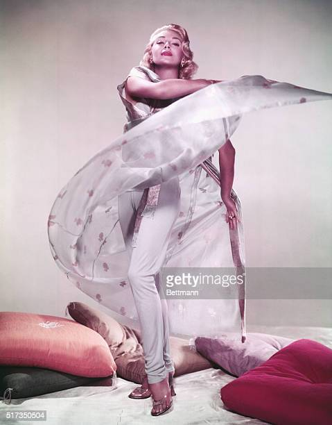 "Full length portrait of American actress Lana Turner , the ""Sweater Girl,"" wearing a white cape and standing near a pile of pillows. Undated..."