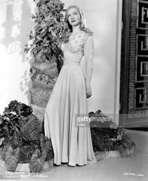 A full length portrait of American actress Veronica Lake posing in evening wear circa 1940