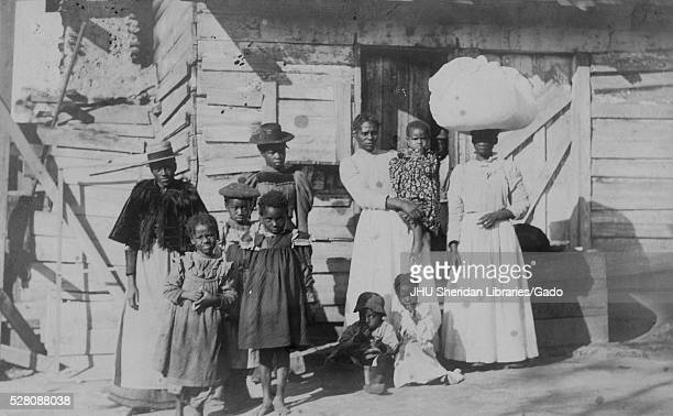 Full length portrait of an African American family one mature woman wearing a hat and dress three young girls wearing dresses one teenage girl in a...