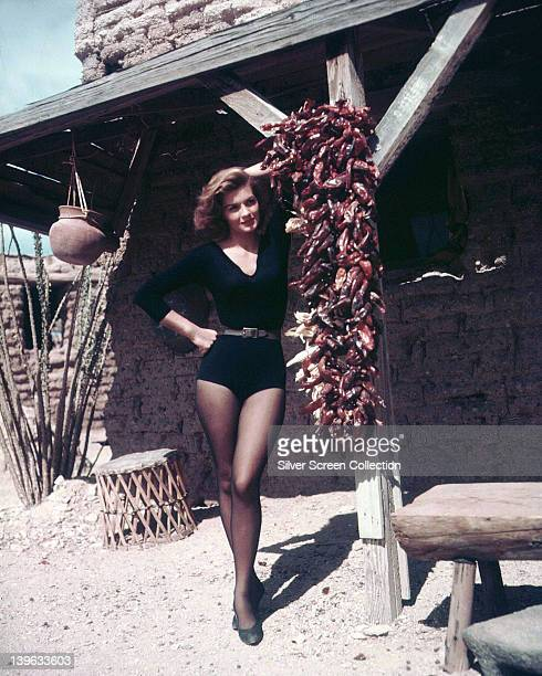 Full length portrait of Angie Dickinson US actress wearing a black longsleeved leotard posing beside a bundle of dried chillies hanging on the set of...