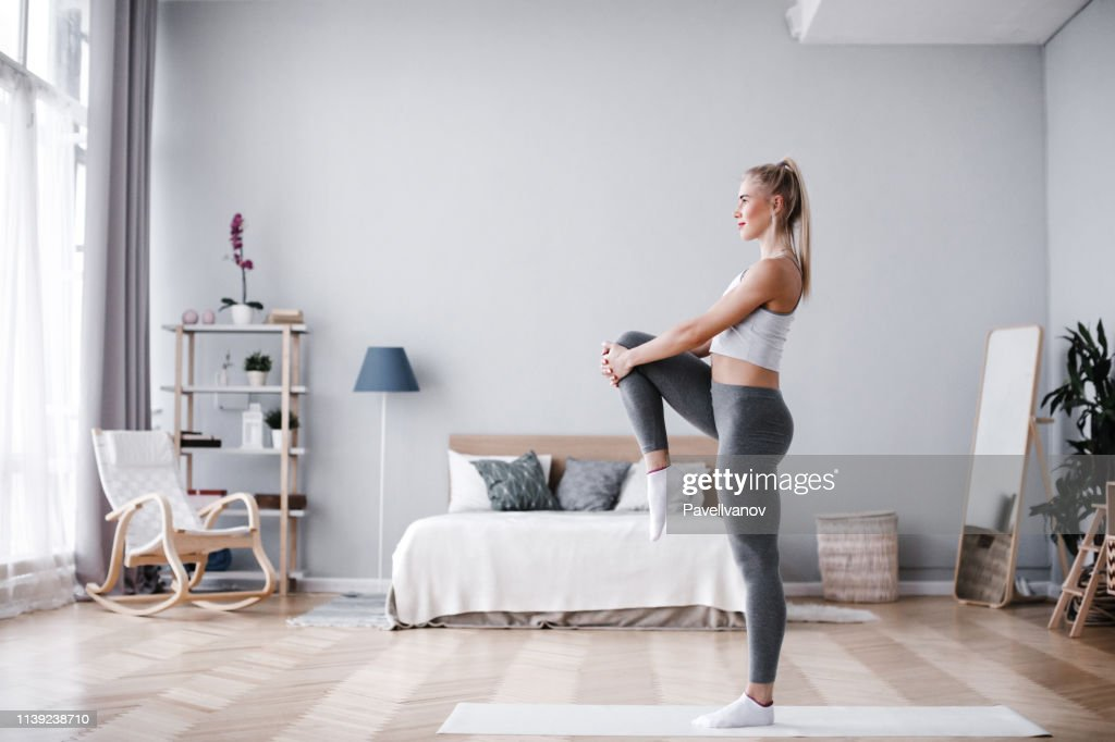 Full length portrait of attractive young woman working out at home, doing pilates exercise on mat. : Stock Photo