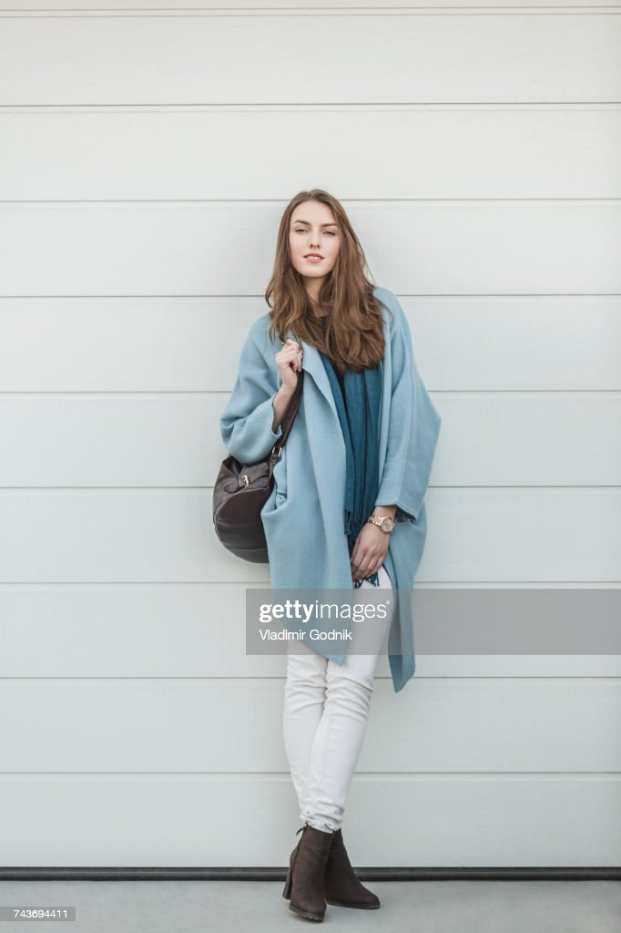 Full length portrait of beautiful woman carrying backpack standing by wall : Stock Photo