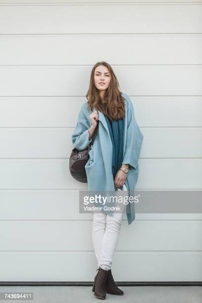 full length portrait of beautiful woman carrying backpack standing by wall - coat fotografías e imágenes de stock