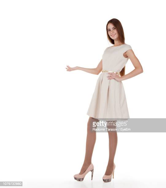 full length portrait of beautiful young woman presenting invisible product against white background - kleid stock-fotos und bilder