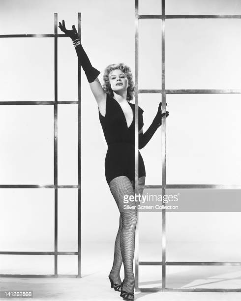 Full length portrait of Betsy Palmer US actress wearing a black leotard with a plunging neckline fishnet stockings and long black gloves posing...