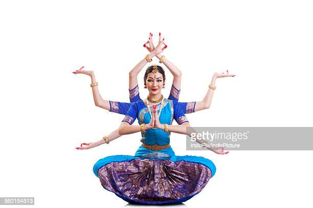 Full length portrait of Bharatanatyam dancer with multiple mudras over white background
