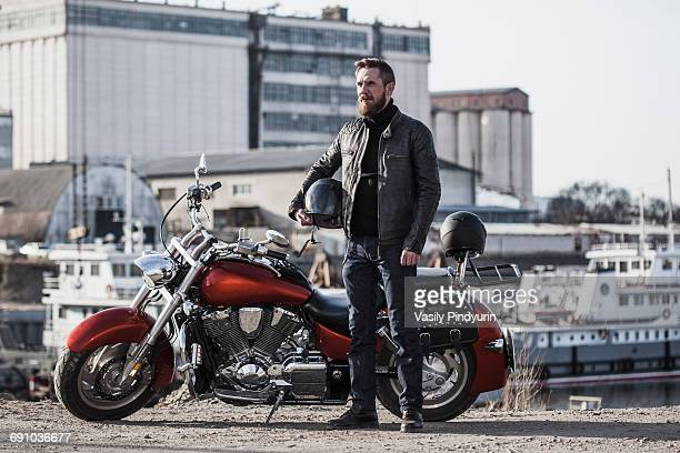 full length portrait of biker holding helmet while standing by motorcycle against industrial setting - バイカー ストックフォトと画像