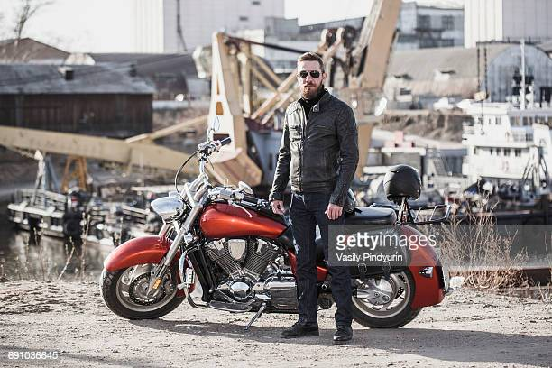 Full length portrait of biker standing by motorcycle against industrial setting