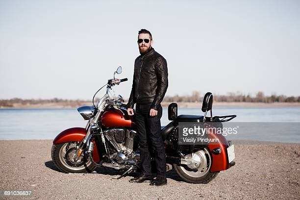 Full length portrait of biker standing by motorcycle at lakeshore