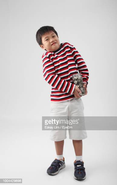 Full Length Portrait Of Boy Holding Jar With Coins On White Background