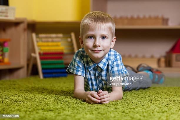 Full length portrait of boy lying on rug in classroom
