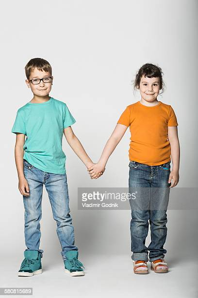 Full length portrait of brother and sister holding hands against white background