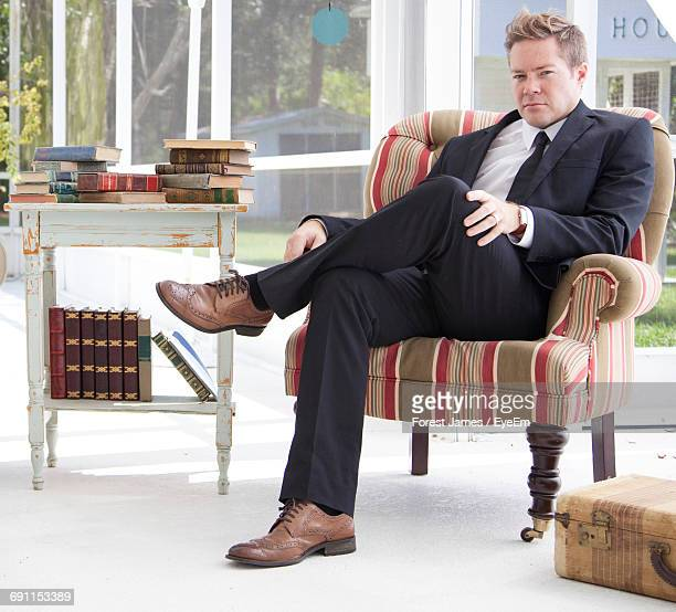 Full Length Portrait Of Businessman Sitting By Books On Chair