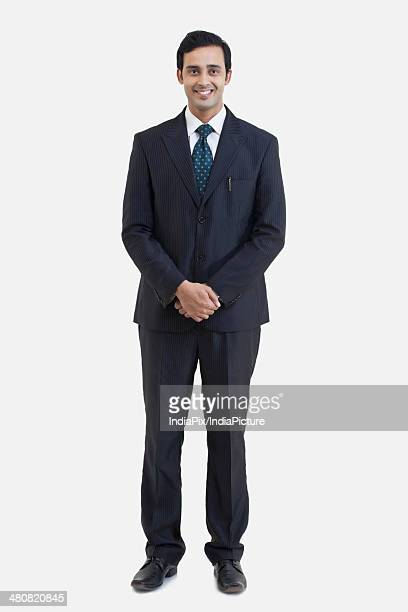 Full length portrait of businessman standing hands clasped over white background