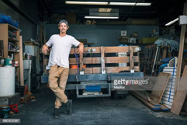 Full length portrait of carpenter leaning on pick-up truck at workshop