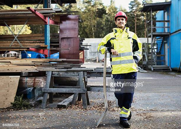 full length portrait of carpentry student leaning on spade outside school building - 18 19 jahre stock-fotos und bilder