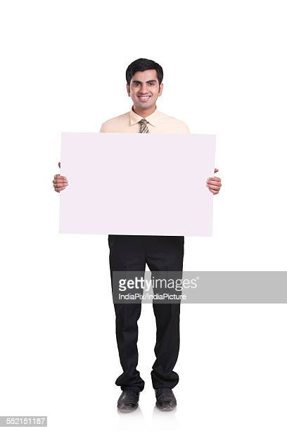 Full length portrait of confident businessman holding blank placard over white background