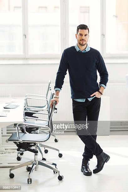 full length portrait of confident businessman leaning on office chair - bürokleidung stock-fotos und bilder