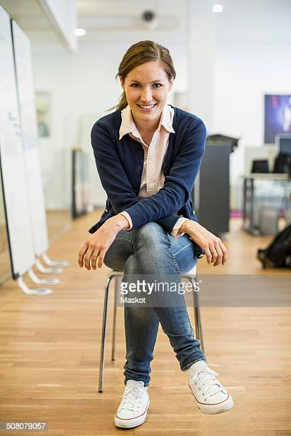 full length portrait of confident businesswoman sitting on chair in office - sitzen stock-fotos und bilder