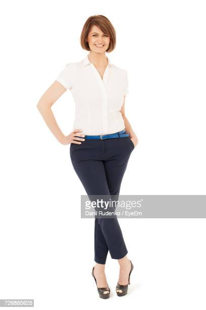 full length portrait of confident businesswoman standing against white background - main sur la hanche photos et images de collection