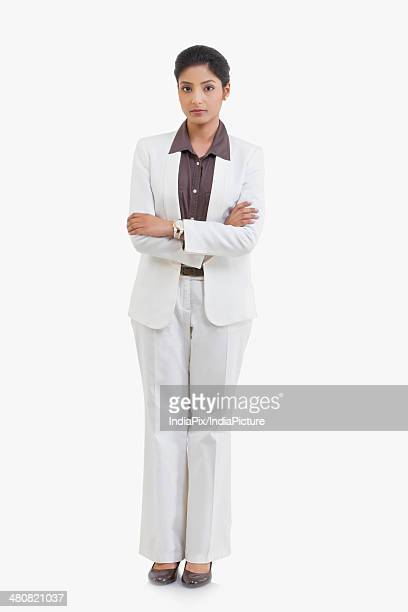 Full length portrait of confident businesswoman standing arms crossed against white background