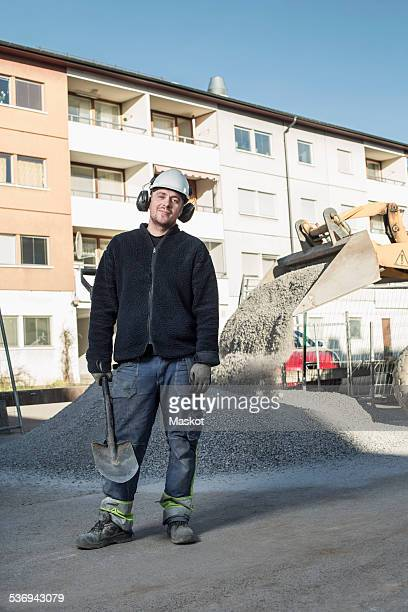 Full length portrait of confident construction worker holding shovel while standing at site