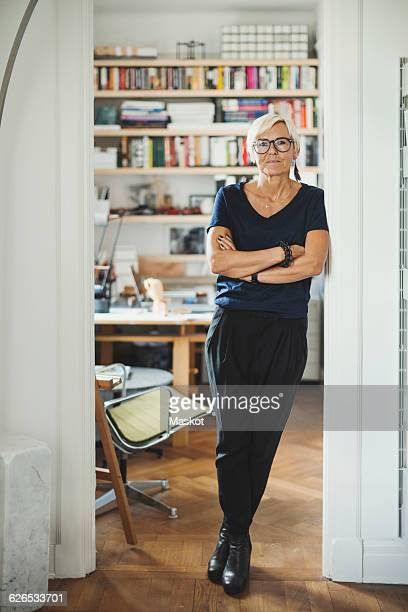 full length portrait of confident designer standing arms crossed at home - doorway stock pictures, royalty-free photos & images