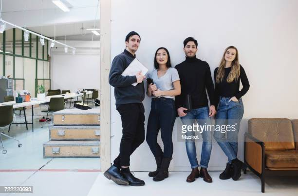 Full length portrait of confident entrepreneurs standing in creative office