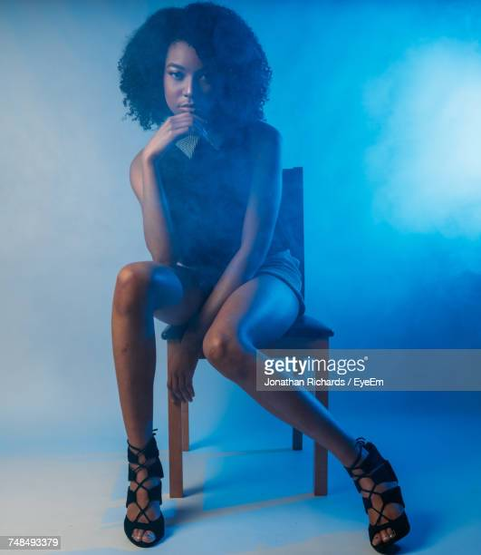 Full Length Portrait Of Confident Fashion Model Sitting On Chair In Illuminated Studio