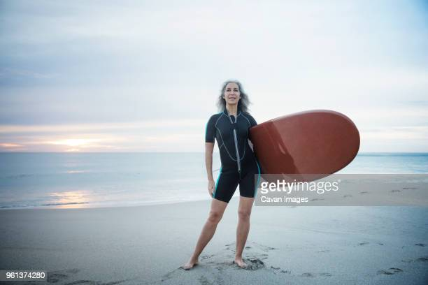 Full length portrait of confident female surfer carrying surfboard at Delray Beach