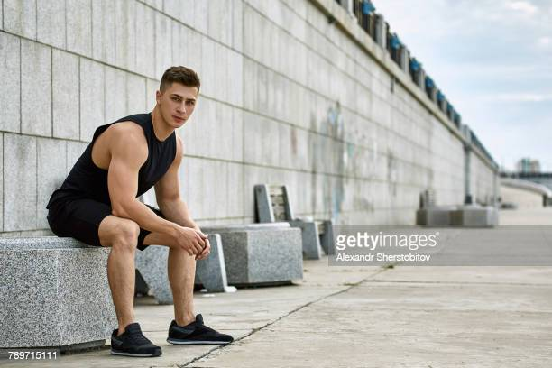 Full length portrait of confident male athlete sitting on seat at footpath