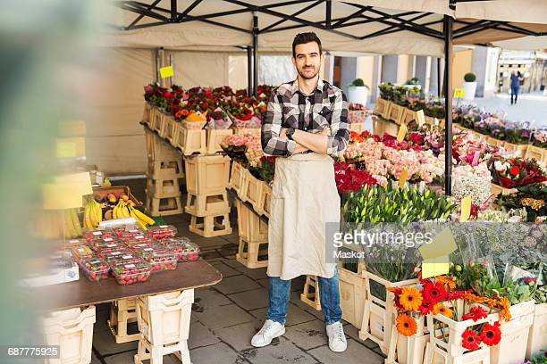 Full length portrait of confident male owner standing arms crossed in flower shop