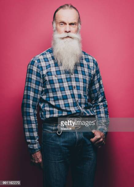 full length portrait of confident senior man standing against pink background - plaid shirt stock pictures, royalty-free photos & images