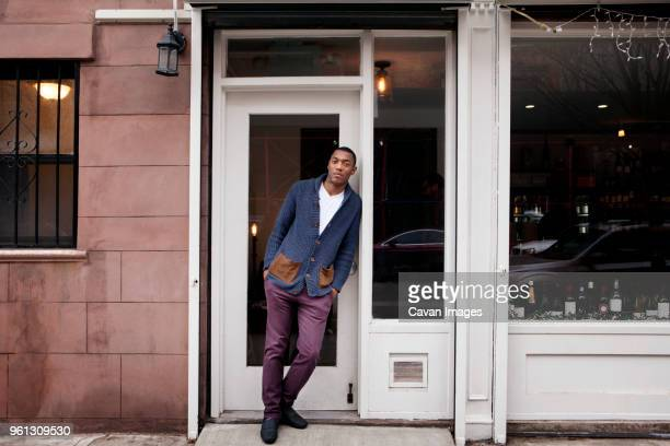 full length portrait of confident small business owner standing at doorway of wine shop - store window stock pictures, royalty-free photos & images
