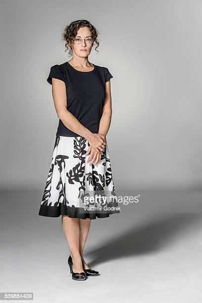 Full length portrait of confident woman standing against gray background